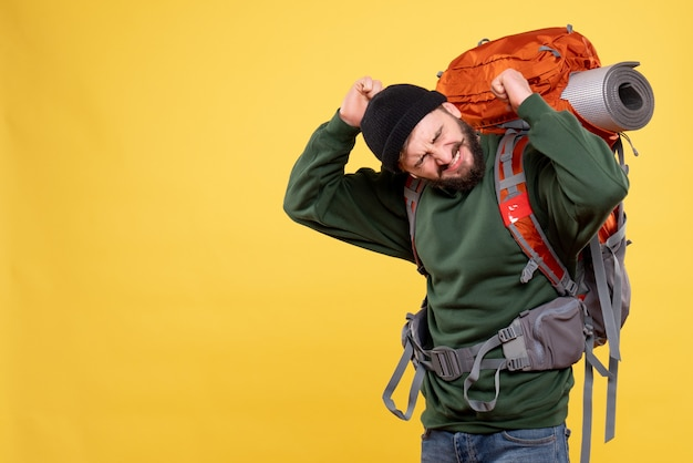 Top view of travel concept with troubled young guy with packpack