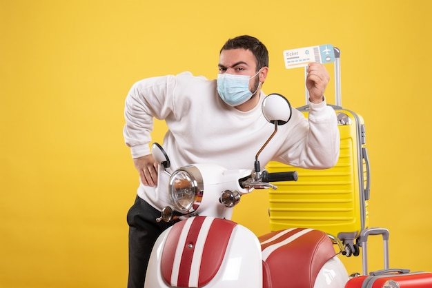 Top view of travel concept with young guy in medical mask standing near motorcycle with yellow suitcase on it and holding ticket