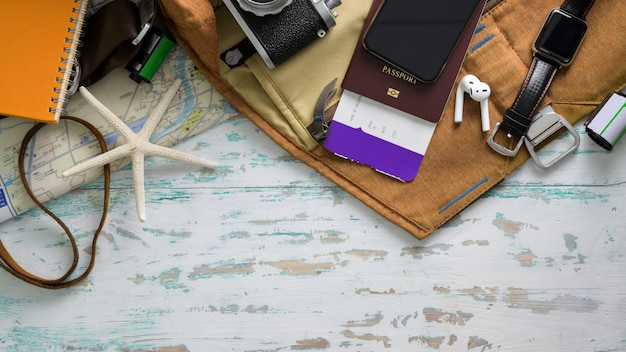 Top view of travel items with smartphone, camera, boarding pass and other travel accessories