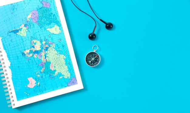 Top view of travel notebook with world map, magnetic compass and headphones on blue. flat lay