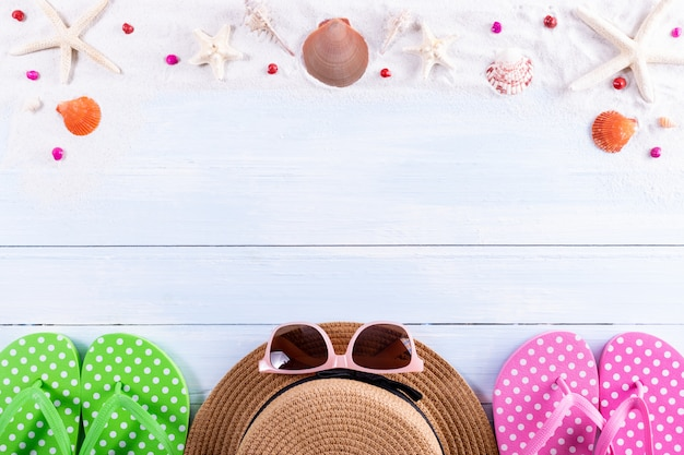 Top view of traveler accessories.sand, starfish and shells on wooden board. summer or travel concept