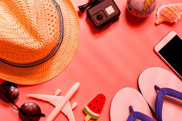 Top view of traveler accessories, tropical palm leaf and airplane on pink background.