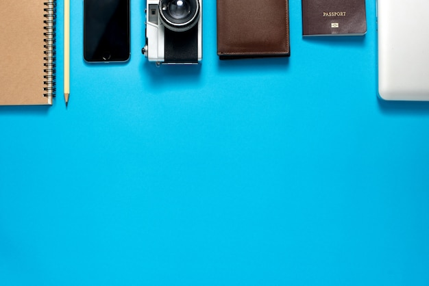 Top view of traveler's accessories on blue background, travel concept background