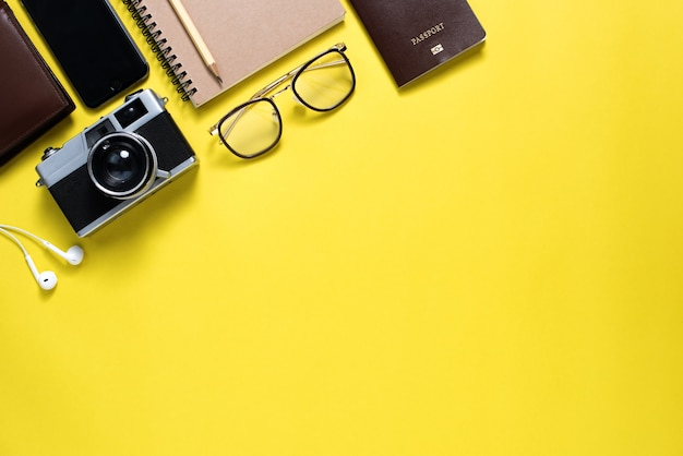 Top view of traveler's accessories on yellow background, travel concept background