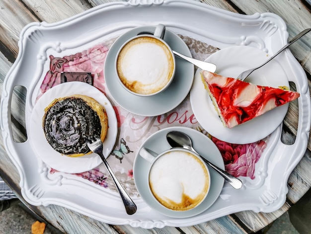 Top view of a tray with cappuccino cups and tasty desserts