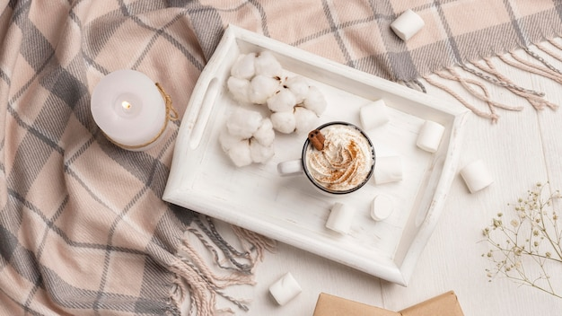 Top view of tray with coffee with whipped cream and candle