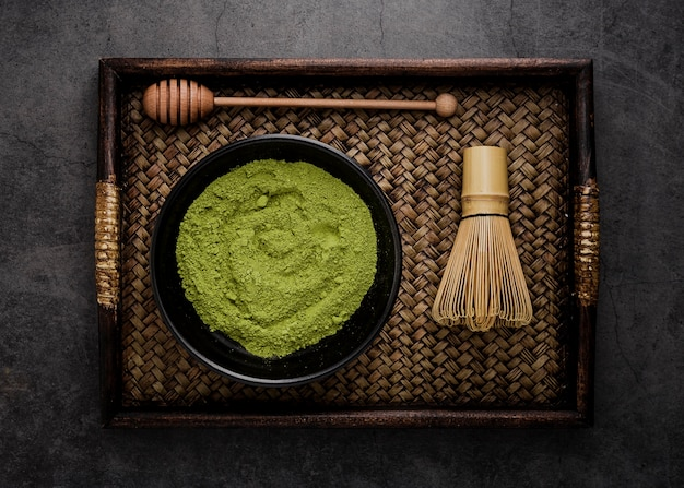 Top view of tray with matcha tea powder in bowl with bamboo whisk