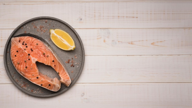 Top view tray with raw salmon steak and lemon with copy-space