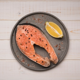 Top view tray with raw salmon steak and lemon