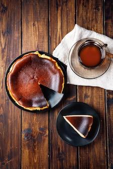 Top view of trendy basque burnt cheesecake on dark wooden background