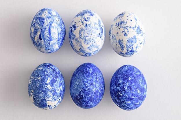 Вид сверху модных шести пасхальных яиц с классическим эффектом синего градиента на белом фоне