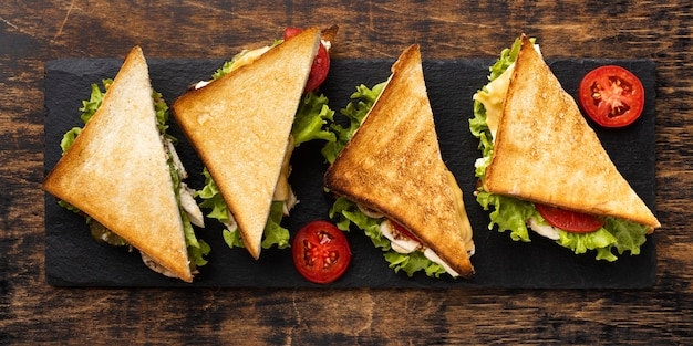Top view of triangle sandwiches on slate with tomatoes