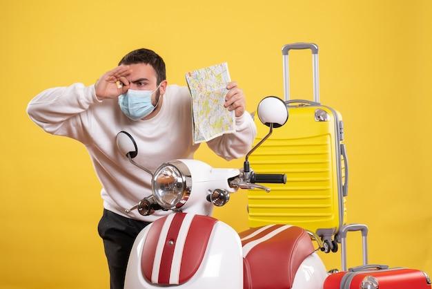 Vista dall'alto del concetto di viaggio con ragazzo concentrato in maschera medica in piedi vicino alla moto con valigia gialla su di essa e con in mano il biglietto