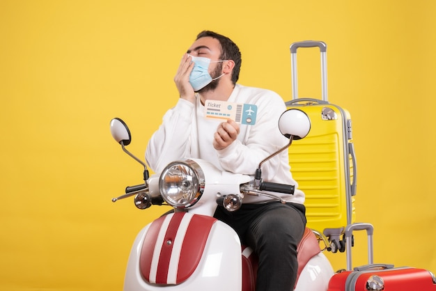 Top view of trip concept with dreamy guy in medical mask sitting on motorcycle with yellow suitcase on it and holding ticket