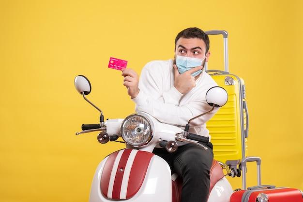 Vista dall'alto del concetto di viaggio con un giovane ragazzo concentrato in maschera medica seduto su una moto con valigia gialla su di esso e in possesso di carta di credito