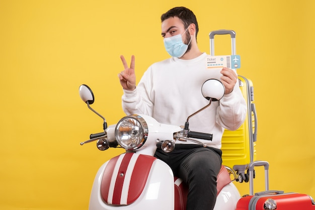Top view of trip concept with young guy in medical mask sitting on motorcycle with yellow suitcase on it and holding ticket making victory gesture