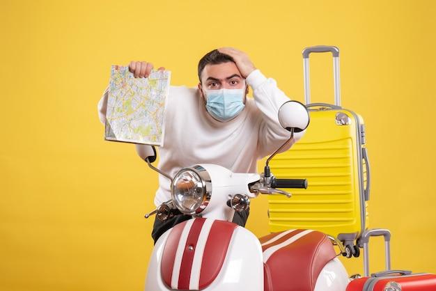Vista dall'alto del concetto di viaggio con un giovane ragazzo in maschera medica in piedi vicino alla moto