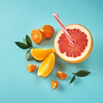 Top view of tropical exotic citrus fruits half a grapefruit, tangerines, orange slices with a plastic straw for juice on a blue paper background.