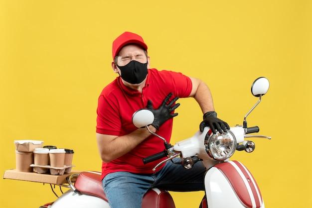 Vista dall'alto del ragazzo tormentato del corriere che indossa la camicetta rossa e guanti del cappello in maschera medica che consegna l'ordine che si siede sullo scooter che soffre di infarto
