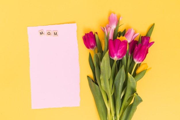 Top view of tulip flowers with blank paper and mom text on wooden blocks above yellow backdrop