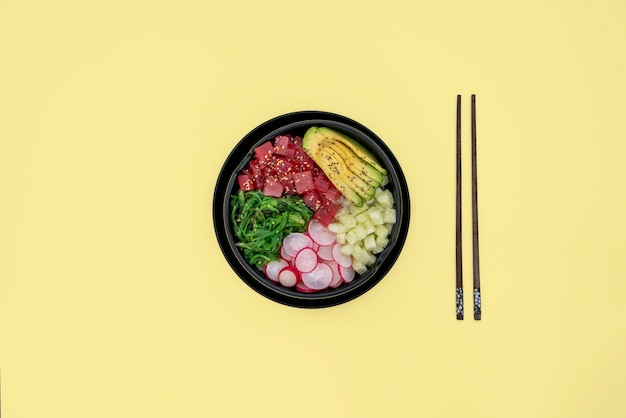 Top view of tuna poke bowl on yellow background