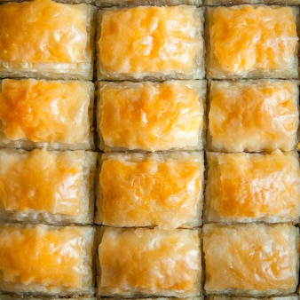 Top view turkish baklava dessert made of thin pastry, nuts and honey