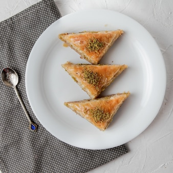 Top view turkish baklava with spoon and rag in round plate