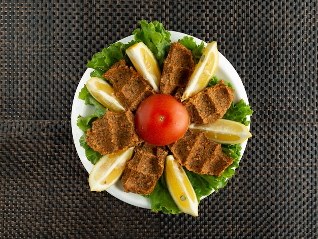 Top view of turkish cig kofte raw meatballs served with lettuce and lemon