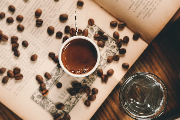 Top view turkish coffee with coffee beans on an open book with a glass of water