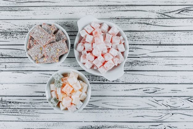 Top view turkish delight lokums in bowls on white wooden background. horizontal
