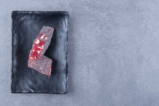 Top view of turkish delight rahat lokum on black plate over grey background.