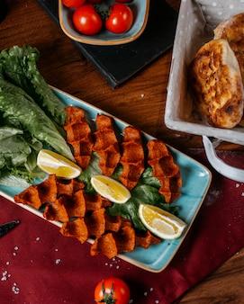 Vista superiore del kofte turco del cig dell'alimento con il limone e la lattuga su una tavola di legno