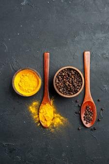 Vista dall'alto curcuma pepe nero in piccole ciotole in cucchiai di legno sulla tavola nera