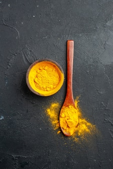 Top view turmeric bowl turmeric in wooden spoon on dark table free place