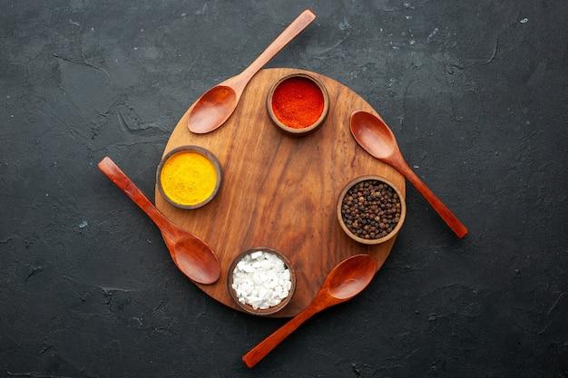 Vista dall'alto curcuma pepe rosso pepe nero sale marino in piccole ciotole quattro cucchiai su tavola rotonda sul tavolo scuro con spazio di copia