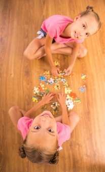 Top view of twins sisters are solving jigsaw puzzle.