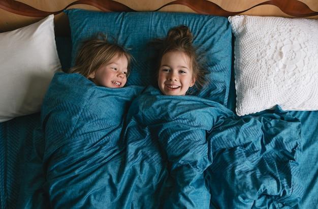 Вид сверху, две очаровательные дочери выглядывают из-под одеяла, лежат вместе на уютной кровати дома, милые детки отдыхают, наслаждаясь досугом в спальне