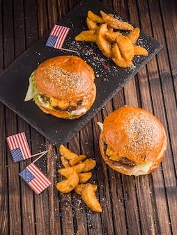 Vista dall'alto di due hamburger americani con patatine fritte