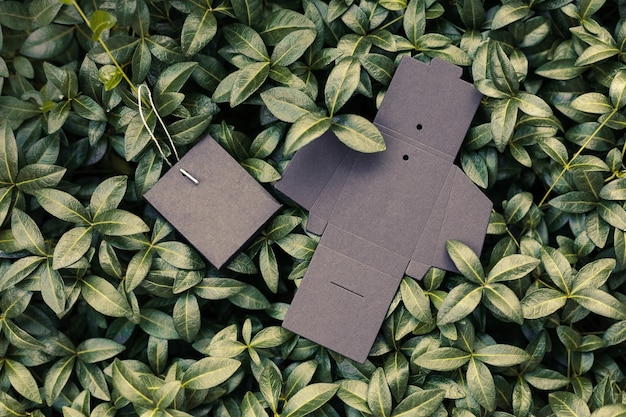 Top view of two black empty unfolded and folded boxes for accessories or tag for clothes on backgrou...