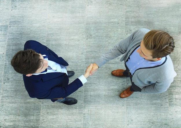 Top view of a two businessman shaking hands. welcome to business.