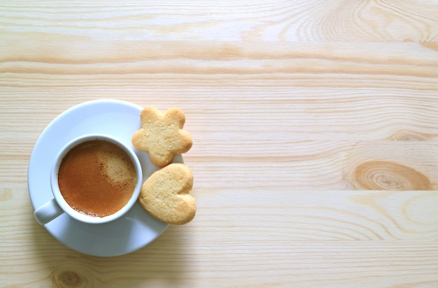 Top view of two butter cookies with a cup of coffee on the wooden table