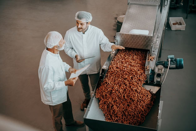 Top view of two caucasian quality controllers standing next to machine with salty sticks and evaluating quality. both are dressed in white uniforms and having hairnets. food plant interior.