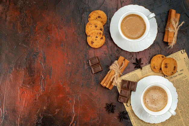 Top view of two cups of coffee cookies cinnamon limes chocolate bars on an old newspaper on the left side on dark background