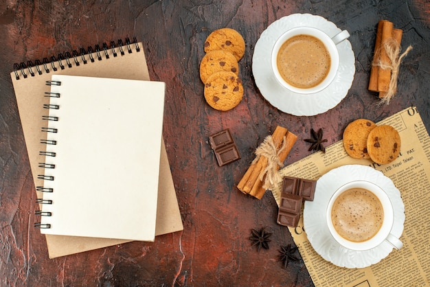 Top view of two cups of coffee cookies cinnamon limes chocolate bars on an old newspaper and notebooks on dark background