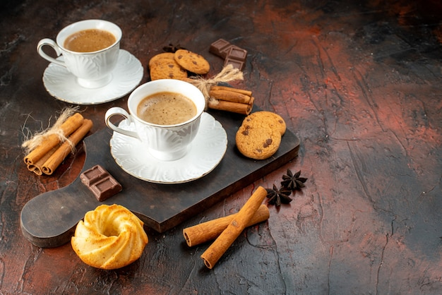 Top view of two cups of coffee cookies cinnamon limes chocolate bars on wooden cutting board on dark background