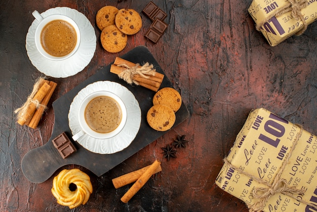Top view of two cups of coffee cookies cinnamon limes chocolate bars on wooden cutting board and gift boxes on dark background