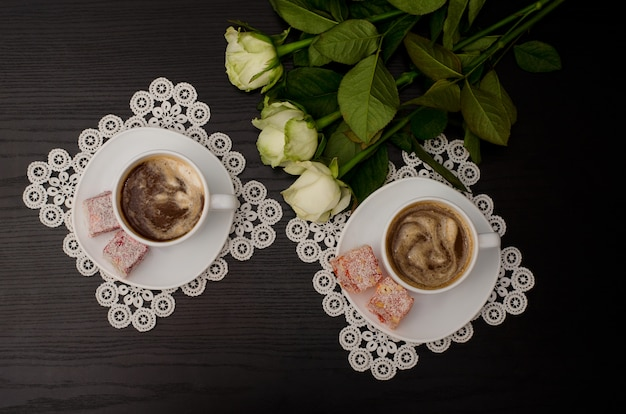 Top view of two cups of coffee with milk, turkish delight on a saucer, white roses