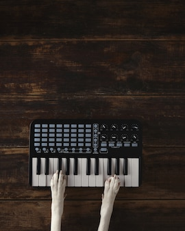Top view two dog paws on midi piano compact wireless keyboard mixer plays melody.