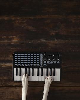 Vista dall'alto due zampe di cane sul mixer tastiera wireless compatto pianoforte midi suona la melodia.