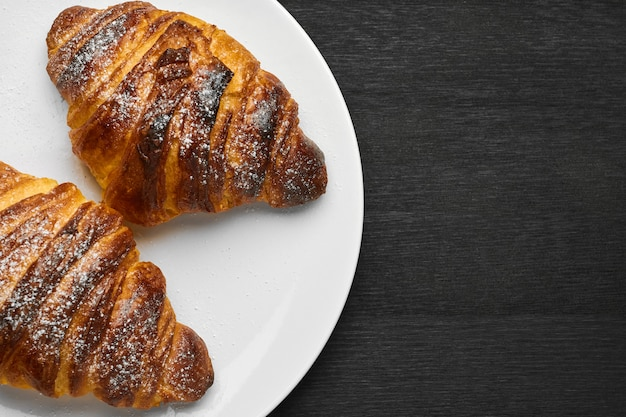 Top view on two fresh french buttery croissant on a white plate on a black wall with copy space